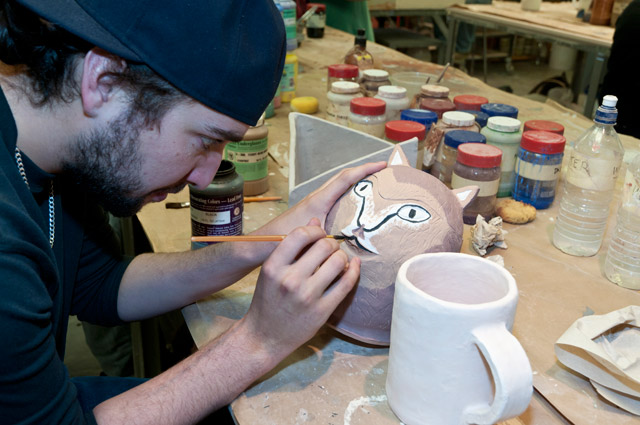 Ceramics student applying glaze to an animal effigy container.