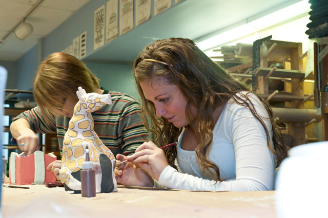 Ceramics student applying glaze to an animal effigy container