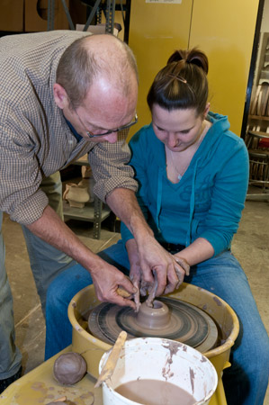 Ceramics instructor helping student throw on the potter's wheel.