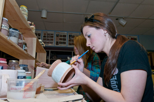 Ceramics I student applying glaze to an animal effigy container.